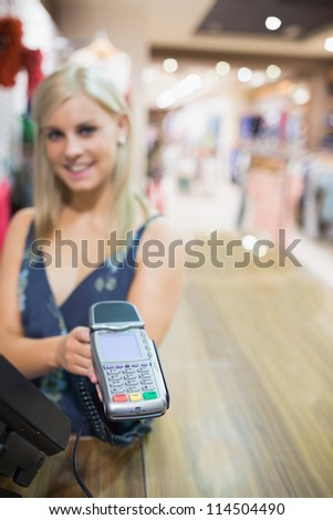 Smiling woman holding credit card machine in clothes store - stock photo