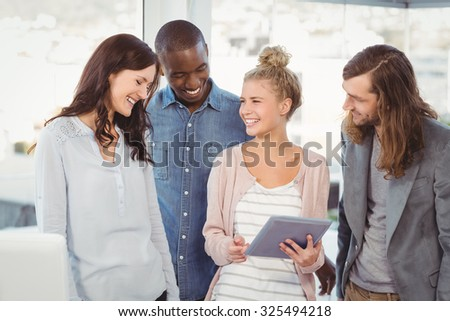 Smiling woman holding digital tablet and discussing with coworkers at office - stock photo