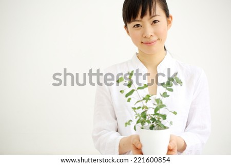 Smiling woman holding flowerpot - stock photo