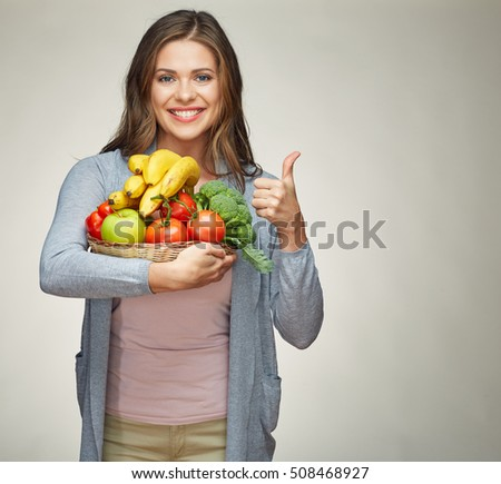smiling woman holding fruit set showing thumb up.