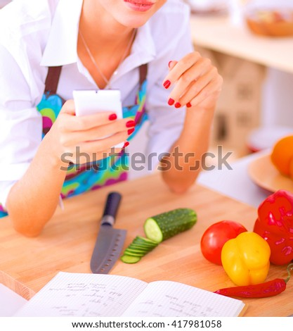 Smiling woman holding her cellphone in the kitchen - stock photo