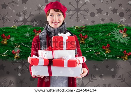 Smiling woman holding large presents against snowflake wallpaper pattern - stock photo