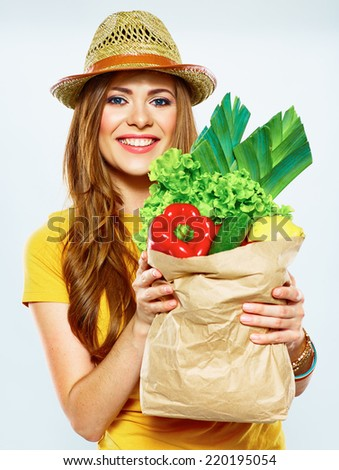 smiling woman holding paper bag with green vegan food . yellow hat . white background .