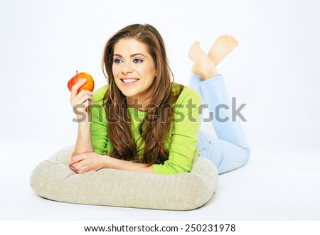 Smiling woman holding red apple lying on a floor. Big smile with teeth. White background isolated. - stock photo