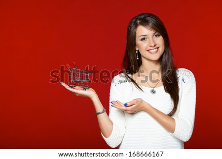 Smiling woman holding shopping cart on her palm, over red background