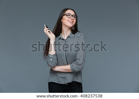 Smiling woman holding smartphone and looking away over gray background - stock photo