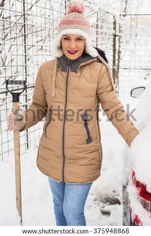 Smiling woman holding snow shovel and standing near car - stock photo
