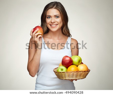 Smiling woman holding straw basket with fruits. Studio isolated.