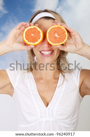 Smiling woman holding two grapefruits in front of eyes