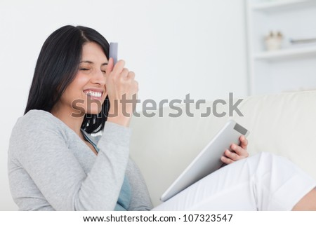 Smiling woman holding up a credit card and a tablet in a living room