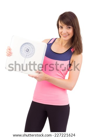 Smiling woman holding weighing scales on white background - stock photo