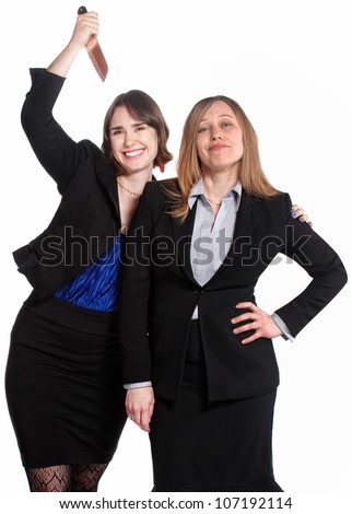 Smiling woman holds a knife behind clueless coworker - stock photo