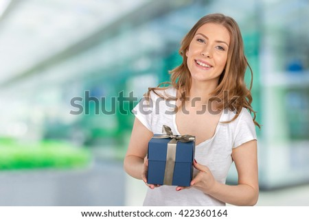 Smiling woman holds  gift box
