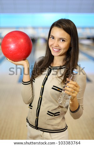 Smiling woman holds red ball and bottle with water in bowling club; shallow depth of field
