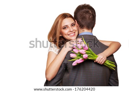 Smiling woman hugging her man and holding a bouquet of tulips. The concept of Valentine's Day - stock photo