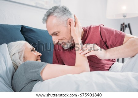 smiling woman hugging husband while resting in bed together