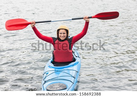 Smiling woman in a kayak cheering at the camera in the middle of a cold lake - stock photo