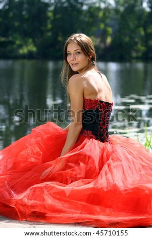 Smiling woman in a red dress sitting near river