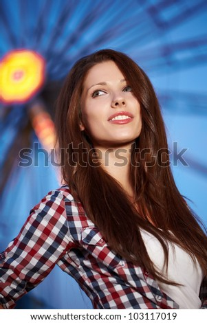 Smiling woman in amusement park. Focus on face.