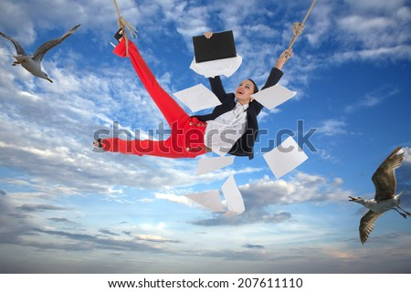 Smiling woman in an office suit holding a rope is flying in the sky with some birds