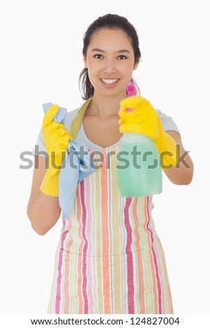 Smiling woman in apron holding out spray bottle - stock photo