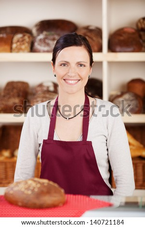 Smiling woman in apron with big bread on the table