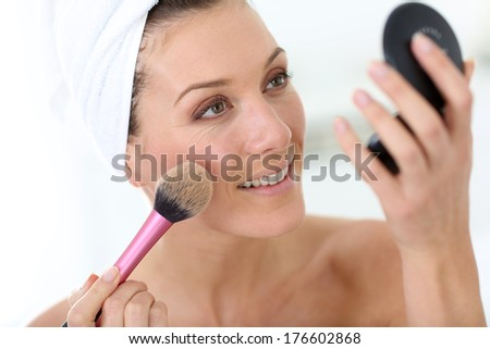 Smiling woman in bathroom applying makeup on - stock photo