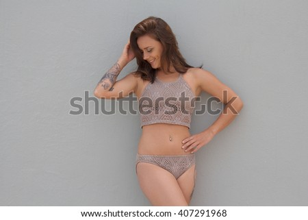 Smiling woman in bikini with tattoos against blank background with copyspace - stock photo