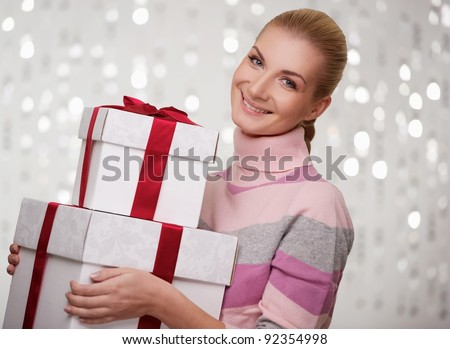 Smiling woman in cashmere sweater with gift boxes. - stock photo