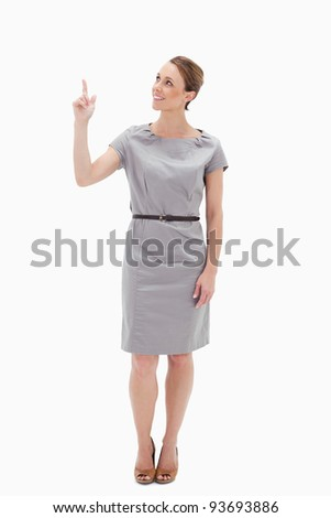 Smiling woman in dress showing something above with her hand against white background
