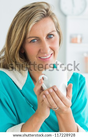 Smiling woman in dressing gown looking directly into the camera - stock photo