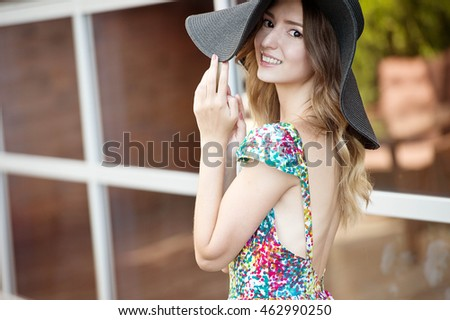 Smiling woman in fashionable look. Woman in straw hat and colorful dress. Summer time