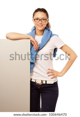 Smiling woman in glasses leaning over blank banner isolated on white background