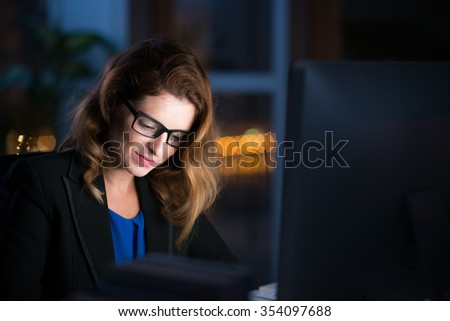 Smiling woman in glasses working late in her office - stock photo