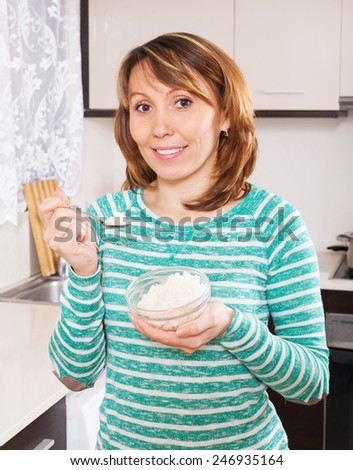 Smiling  woman in green eating boiled rice in kitchen