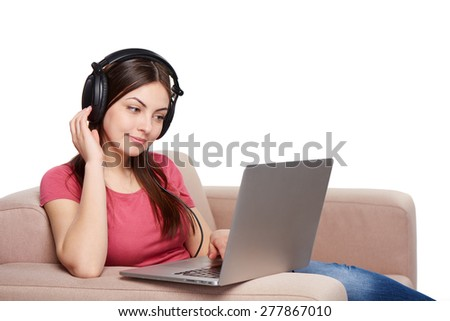 Smiling woman in headphones sitting on sofa using laptop, over white background - stock photo