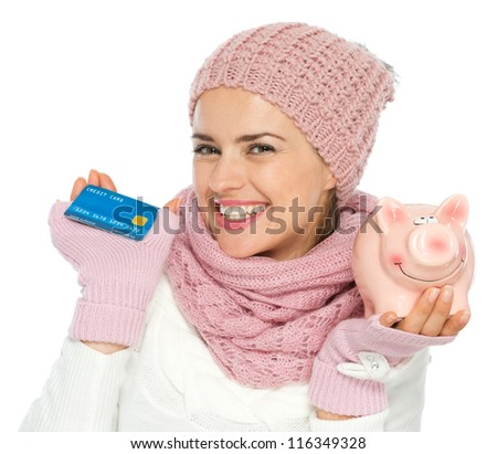 Smiling woman in knit winter clothing holding credit card and piggy bank - stock photo