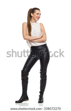 Smiling Woman In Leather Trousers Looking Away. Full length studio shot isolated on white. - stock photo