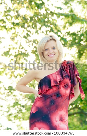 smiling woman in outdoors with green leaves in the background