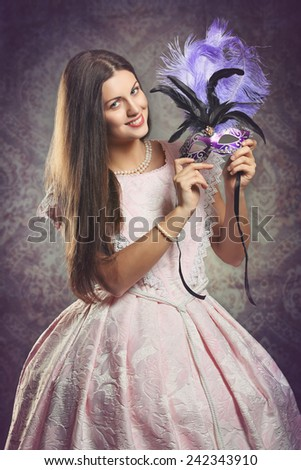 Smiling woman in pink historical dress with purple venetian mask . Venice textured portrait