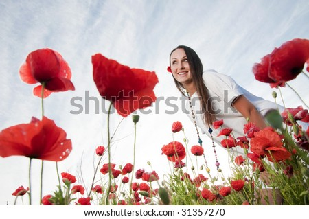 Smiling woman in poppy field - stock photo