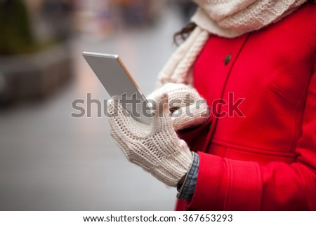 Smiling Woman in Red Coat and and wool cap and gloves read messages on smart phone and smiling. Urban Space. Cold Weather