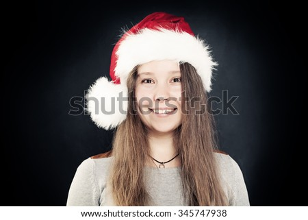 Smiling Woman in Santa Hat on Dark Background. Real People. Christmas