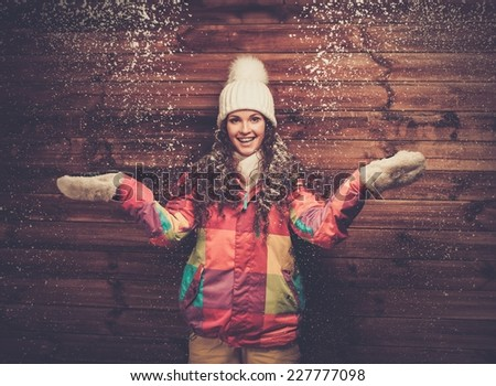 Smiling woman in ski jacket and white hat standing against wooden house wall under snow  - stock photo