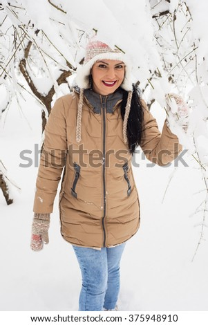 Smiling woman in snow outside in park - stock photo