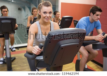 Smiling woman in spin class with others in gym - stock photo