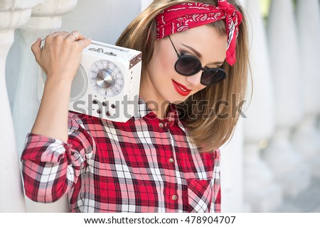 Smiling woman in sunglasses and red bandana and a plaid shirt. Beautiful girl with pretty smile holding retro tape recorder.
