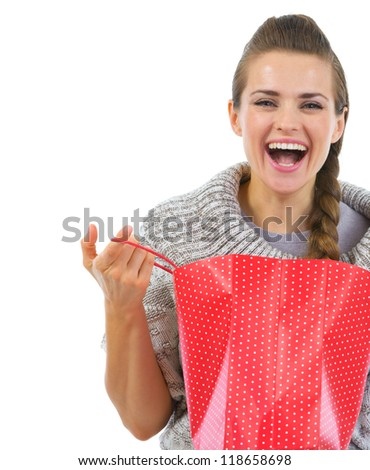 Smiling woman in sweater opening shopping bag - stock photo