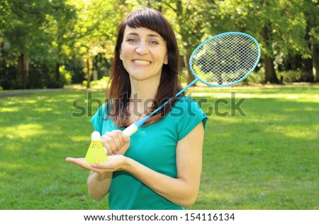 Smiling woman in the sunny park with badminton racket and badminton shuttlecock with plastic feathers - stock photo
