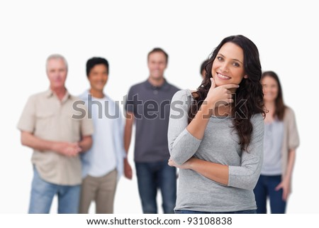 Smiling woman in thinkers pose and friends behind her against a white background - stock photo